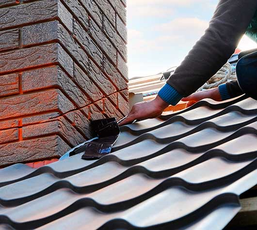 Roofer Attaching Metal Sheet to Chimney
